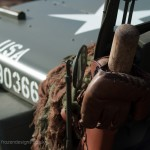 The bonnet of a jeep with a whilte star and USA markings, a baseball bat and glove hanging off the side.