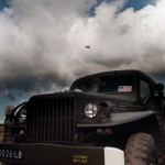 A low angle shot of a military truck whilst a plan flys across the cloudy sky