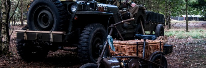 A young paratrooper sat in a jeep with a small collapsable motorbike in front.